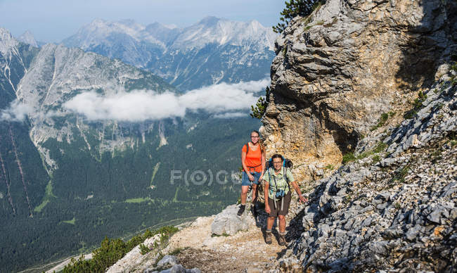 Mujeres excursionistas en camino, Mittenwalder Hohenweg, Karwendel, Mittenwald, Alemania, Europa - foto de stock