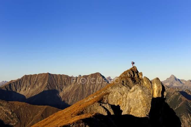 Climber della montagna su un picco — Foto stock