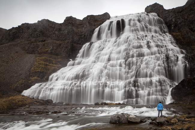Hiker in front of the Dynjandi waterfall — Stock Photo