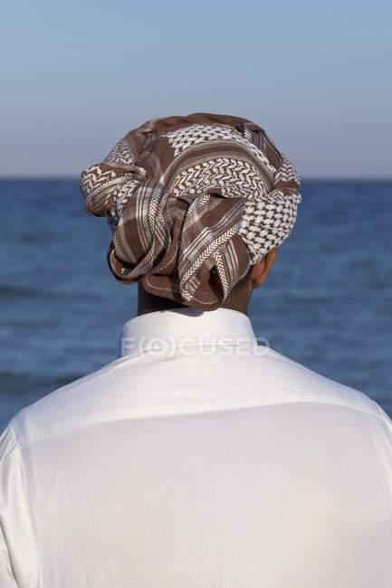 Vista posteriore dell'uomo in turbante guardando il paesaggio marino — Foto stock
