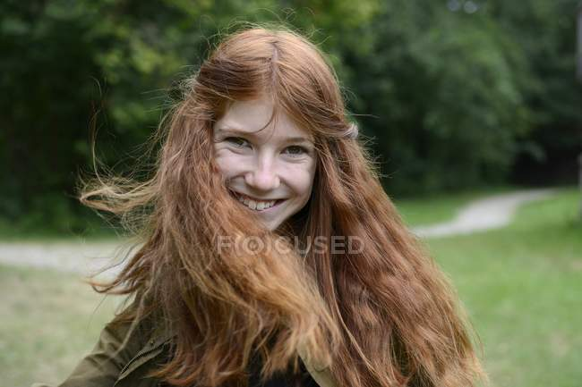 Teenage girl flicking long red hair — Stock Photo