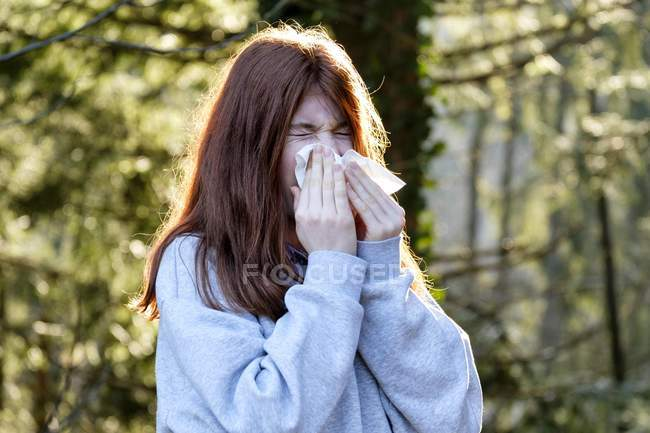 Teen girl wiping nose with napkin — Stock Photo