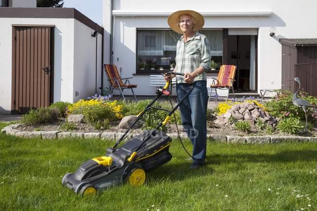 Female gardener mowing lawn grass — Stock Photo