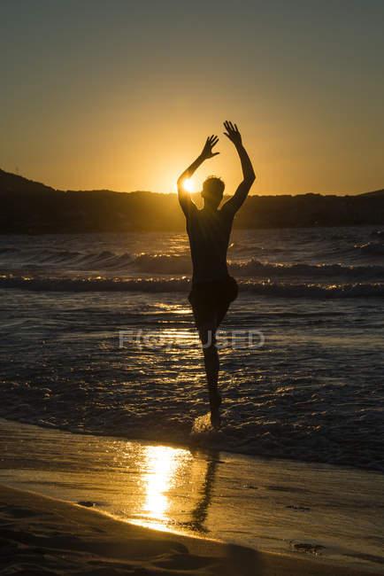 Silueta de hombre que salta en el agua de mar al atardecer, Córcega, Francia - foto de stock