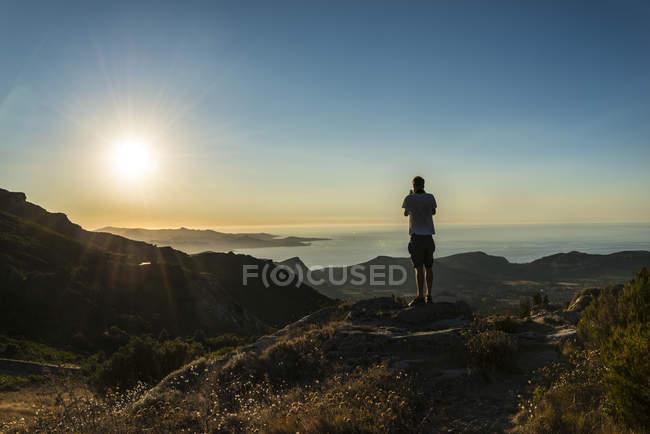 Hombre de fotografiar la puesta de sol por el mar en Córcega, Francia - foto de stock