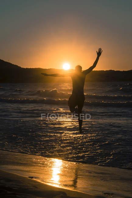 Vista posterior del hombre saltando en el agua en la playa al atardecer, Córcega, Francia - foto de stock
