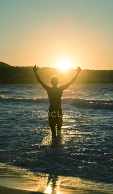 Vista posterior del hombre levantando los brazos en la playa al atardecer, Córcega, Francia - foto de stock