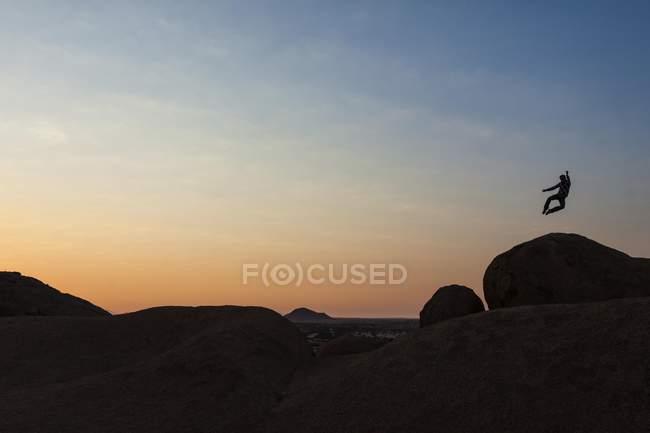 Hombre que salta sobre una roca de granito - foto de stock