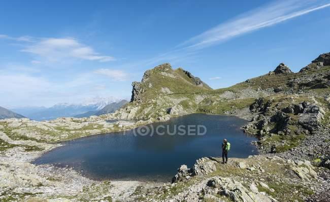 Caminante por un lago de montaña - foto de stock