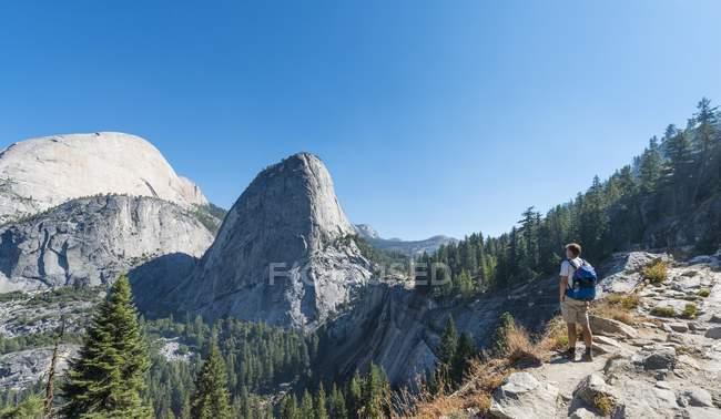 Walker looking on Liberty Cap, Yosemite National Park, California, USA — Stock Photo