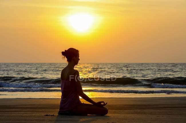 Mujer meditando en la playa al atardecer, Kerala, India, Asia - foto de stock