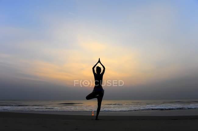 Mujer haciendo la pose del árbol de yoga en la playa al atardecer, Kerala, India, Asia - foto de stock