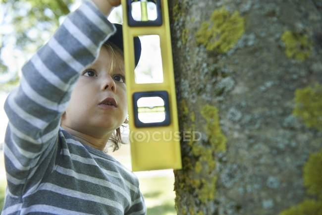 Мальчик с ствол дерева для измерения уровня духа — стоковое фото