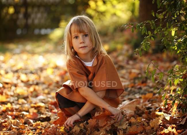 Девочка сидит в осенней листвой — стоковое фото