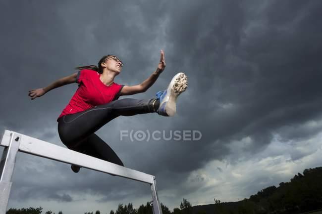 Athlete jumping hurdles — Stock Photo