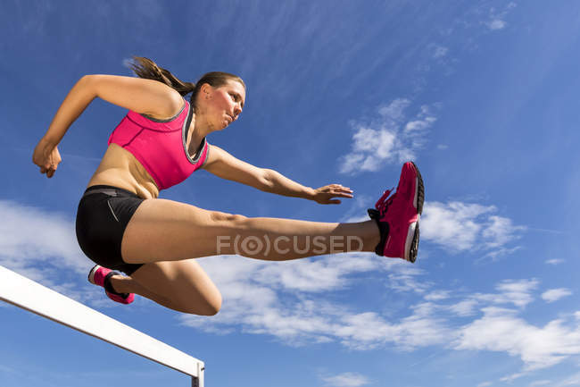 Young woman hurdling — Stock Photo