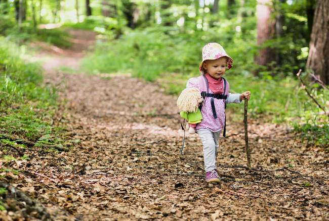 Girl with doll and walking stick — Stock Photo