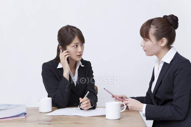 Two asian businesswomen using phone while meeting — Stock Photo