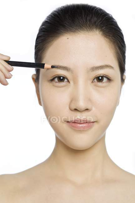 Asian model with natural makeup coloring eyebrows — Stock Photo