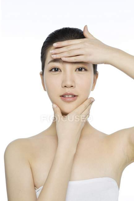Asian model with natural makeup touching face — Stock Photo