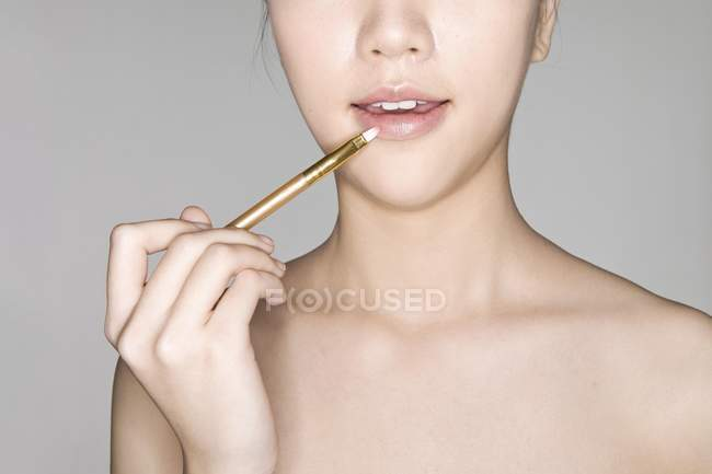 Asian model with natural makeup coloring lips — Stock Photo