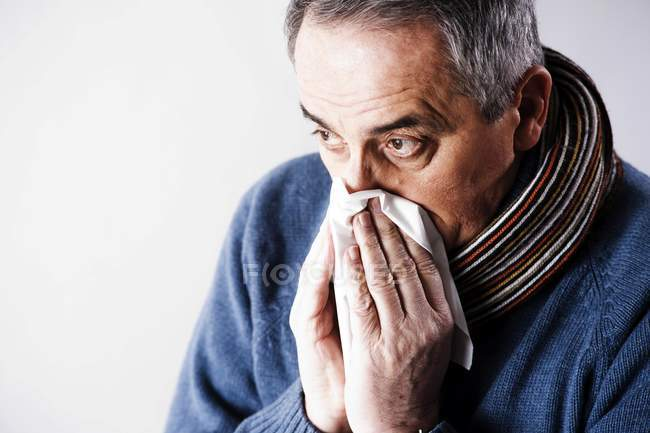 Elderly man blowing nose — Stock Photo