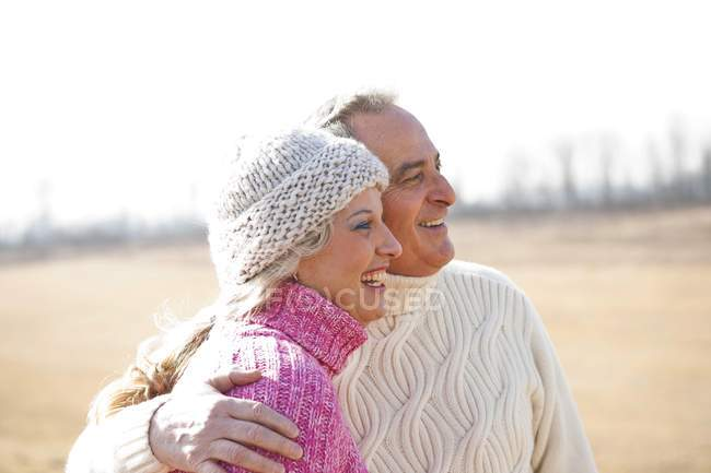 Embracing senior couple in warm sweaters looking away outdoors — Stock Photo