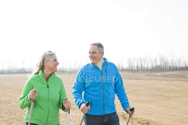 Senior couple nordic walking with poles in field — Stock Photo