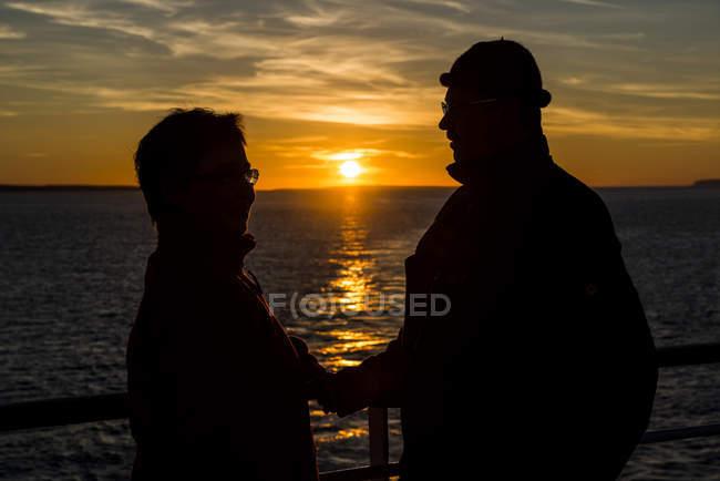 Couple senior à la balustrade du paquebot, regardant les uns les autres tout en regardant le coucher du soleil — Photo de stock