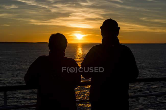Heckansicht des reifes Paar am Geländer des Kreuzfahrtschiff Sonnenuntergang — Stockfoto