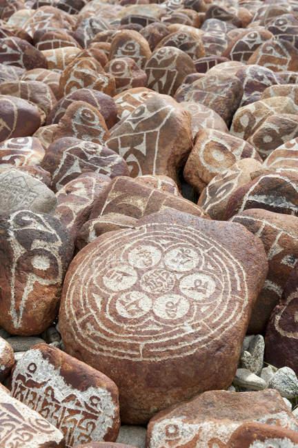 Piedras Mani con escritura tibetana en Tíbet, Asia - foto de stock