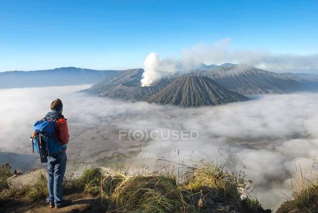 Randonneur devant un paysage volcanique avec fumer volcan Mont Bromo à Java, en Indonésie, Asie — Photo de stock
