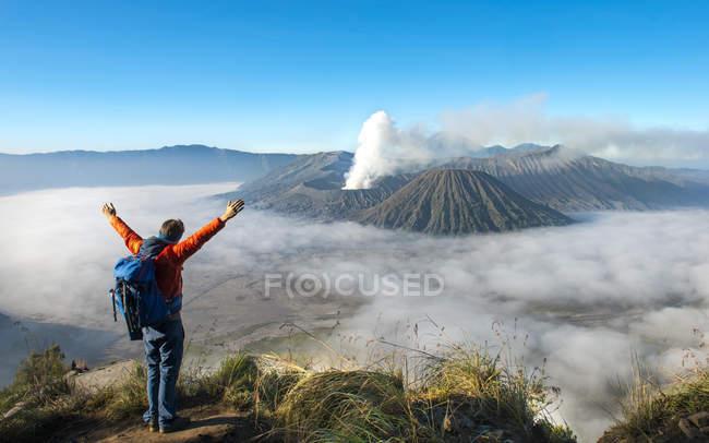 Randonneur avec les bras levés devant un paysage volcanique avec fumer volcan Mont Bromo à Java, en Indonésie, Asie — Photo de stock