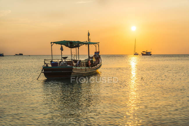 Fishing boats in sea at sunset — Stock Photo