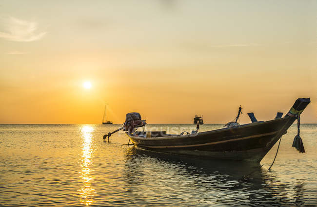 Long-tail boat in sea at sunset — Stock Photo