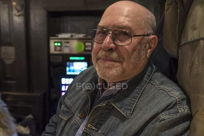 Uomo maggiore in occhiali e denim giacca guardando a porte chiuse — Foto stock