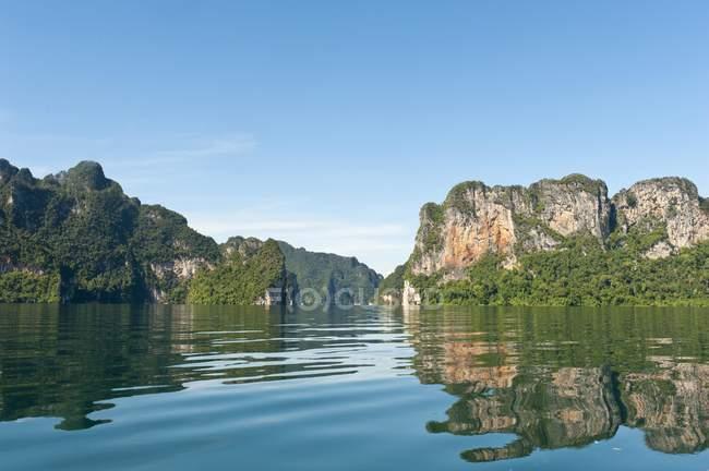 Boscose montagne calcaree che riflette in acqua di lago Chiao Lan, Khao Sok, Thailandia — Foto stock