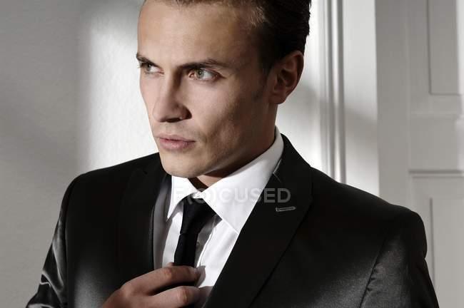 Man in black suit straightening tie, portrait — Stock Photo