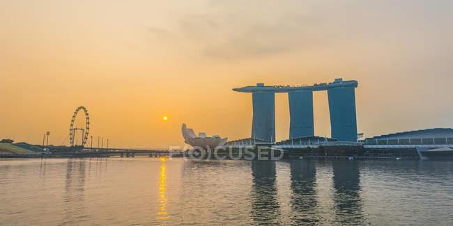 Rueda de la fortuna y el Marina Bay Sands Hotel en sunrise, Singapur, Asia - foto de stock
