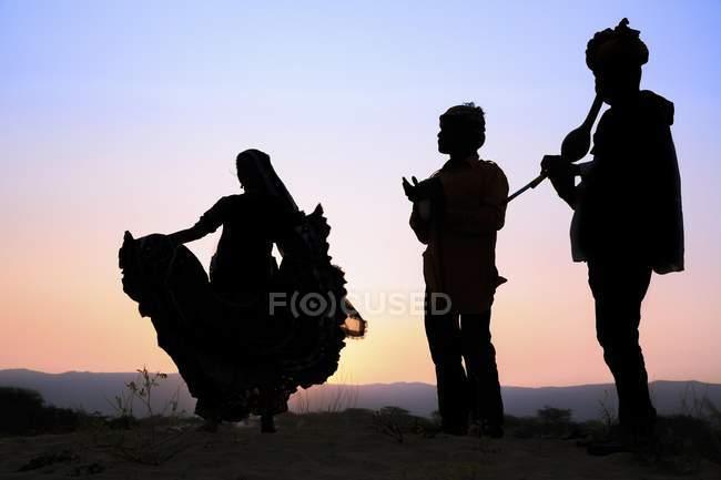 Mulher dançando na frente do sol com músicos, Pushkar justo camelo, Rajastão, Índia — Fotografia de Stock