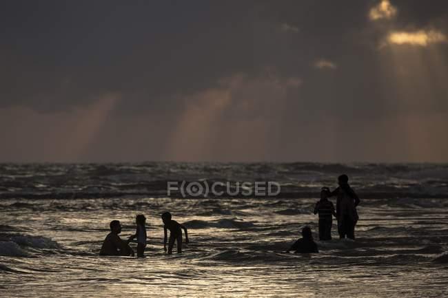 People in water with dark clouds over sea beach, Beruwela, Sri Lanka, Asia — Stock Photo