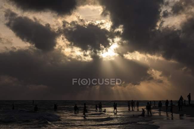 Personas en contraluz en la playa con las nubes oscuras sobre el mar, Beruwela, Sri Lanka, Asia - foto de stock