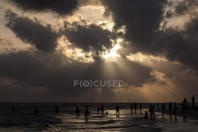 People in backlight on beach with dark clouds over sea, Beruwela, Sri Lanka, Asia — Stock Photo