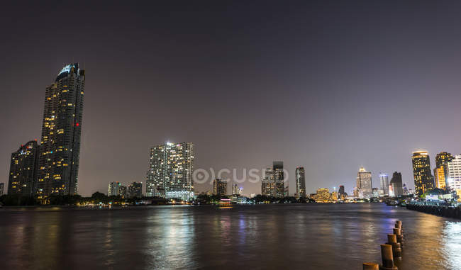 River promenade in evening with Ferris wheel and skyline of Bangkok, Thailand — Stock Photo
