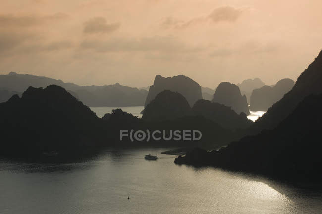 Boat on water at sunset in Ha Long Bay with limestone cliffs, Gulf of Tonkin, Vietnam, Asia — стокове фото