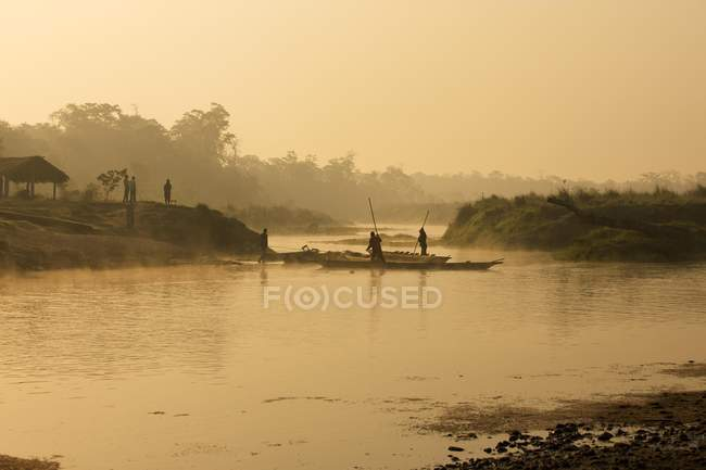 Dugout canoes with ferrymen crossing river in morning, Chitwan National Park, Nepal, Asia — Stock Photo