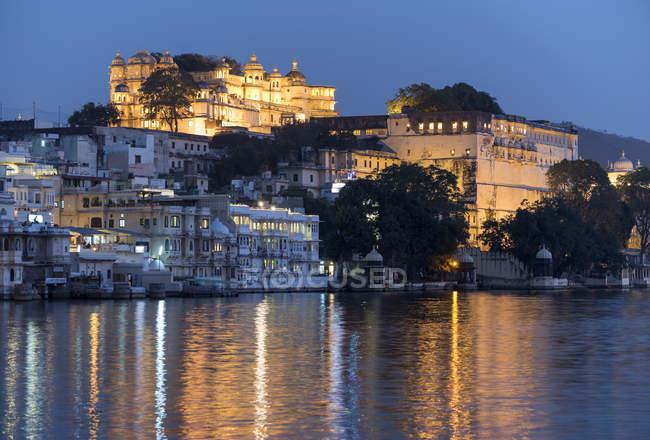 Palazzo di città illuminata sulla riva del lago Udaipur, Rajasthan, India, Asia — Foto stock