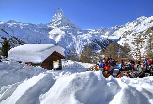 Berghütte mit Touristen auf der Sonnenterrasse mit Blick auf das Matterhorn in Zermatt, Wallis, Schweiz, Europa — Stockfoto