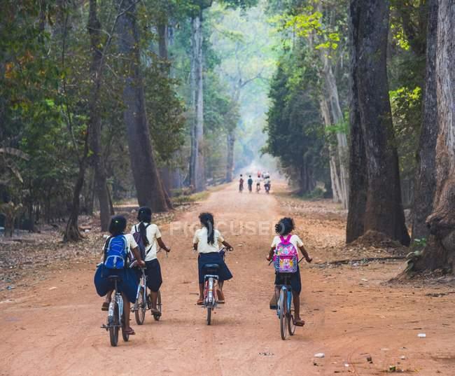 Crianças locais, andar de bicicleta no Parque Arqueológico de Angkor, no Camboja, Ásia — Fotografia de Stock