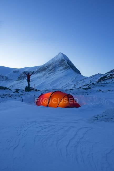 Carpa iluminada con silueta de persona en la nieve en el sendero Kungsleden, Suecia - foto de stock